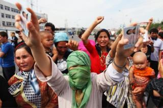 An Uighur woman holds the IDs of her relatives who are currently detained, as she and others protest on a street in July, 2009