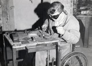 A man in a wheelchair soldering
