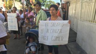 """Pessoas fazem manifestação em rua da Venezuela. Entre elas, mulheres seguram cartazes em que se lê """"sem água, sem luz, sem gás, sem transporte, sem dinheiro"""" e o salário não dá nem para comida"""""""