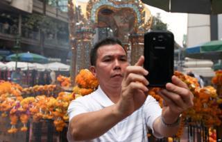 Man takes a selfie at Erawan shrine