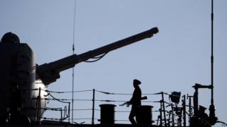 A Russian Navy member stands guard on the deck of the Pyotr Velikiy (Peter the Great) Russian nuclear-powered missile cruiser docked in the Cypriot port of Limassol, on 12 February 2014
