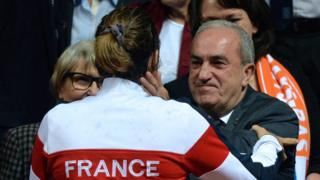 "French Tennis Federation president Jean Gachassin (back) congratulates France""s Fed Cup captain Amelie Mauresmo after France won the Fed Cup semi-final against the Netherlands in Trelaze, northwestern France, on April 17, 2016."