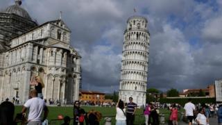 Tourists pose for photographs at the Leaning Tower of Pisa
