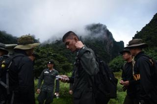 Thai soldiers and police gather in the mountains near the Tham Luang cave
