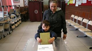 A woman cats vote with her son for the local elections in Ankara