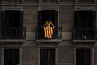 Mujer en un balcón de Barcelona con la bandera catalana.
