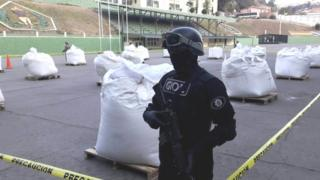 member of Bolivian special forces stands next to bags of cocaine at the police headquarters in La Paz (01 August 2016)