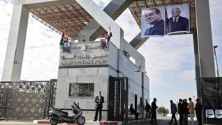 Portraits of Egyptian President Abdel Fattah al-Sisi and Palestinian leader Mahmoud Abbas hang at the Rafah border crossing with Egypt on 1 November 2017
