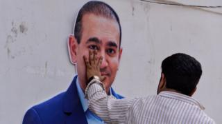 An Indian supporters of the Congress Party keeps his hand on the face of a cut out of billionaire jeweller Nirav Modi during a protest in New Delhi on February 16, 2018.