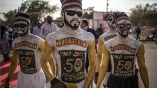 Performers arrive to the entrance of the venue where the opening ceremony of the FESPACO Panafrican Film and Television Festival of Ouagadougou is about to start, on February 23, 2019.