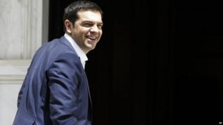 Greece's Prime Minister Alexis Tsipras smiles as he arrives at Maximos Mansion in Athens on Tuesday, June 23, 2015
