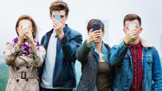 Jovens com o celular na frente do rosto