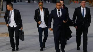 Neymar and his father arriving at court flanked by other men in suits