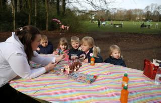Erin Gatling (C) blows out the candles on her 7th birthday cake as she has an impromptu party in her local park after her original party venue was closed amid the coronavirus disease (COVID-19) outbreak in Manchester