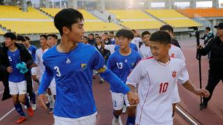 Players of the April 25 Sports Club of North Korea (white) and the Gangwon-do team of South Korea (blue) run together