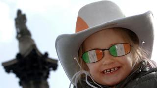 Little girl in novelty Irish sunglasses in front of Nelson's column