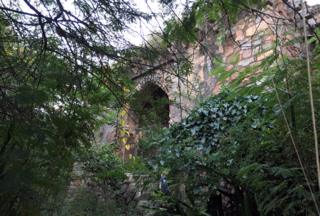 Brickwork of the lodge visible through trees