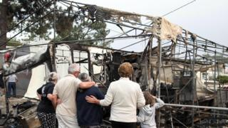 People view damage caused by fires at a camping ground in the Marinha Grande area of central Portugal