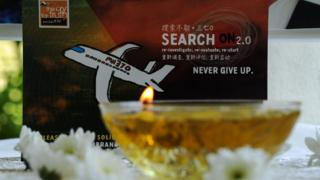 A candle burns a prayer message for passengers of missing Malaysia Airlines flight MH370 in Petaling Jaya on March 8, 2016