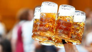A waiter carries glasses of beer during the opening day of Oktoberfest in Munich