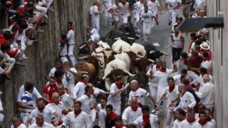 Runners try to avoid bulls of the Puerto de San Lorenzo bull ranch as they run down a street during the traditional San Fermin bull run