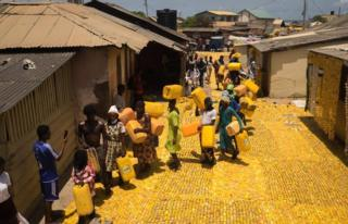 People queuing with jerrycans on yellow tapestry created by artist Serge Attukwei Clottey on a road in La - Accra, Ghana