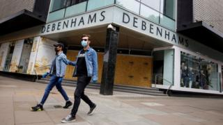 Two people wearing masks walk past a boarded-up Debenhams store in Oxford Street, London