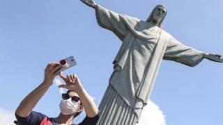 Pessoa com máscara tira foto no Cristo Redentor