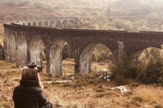 Little girl watching the Jacobite train passing over Glenfinnan viaduct