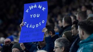 A fan holds up a sign during the English Premier League soccer match between Leicester and Liverpool at The King Power Stadium in Leicester,