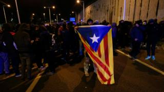 A man holds a Catalan pro-independence Estelada flag as pro-independence protesters block a road in Barcelona on December 21, 2018