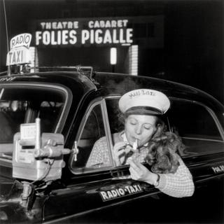 A woman sits in a taxi driver seat and lights a cigarette