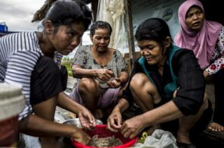 Members of the Trapang Sangke Community prepare fish and shrimp for an evening meal