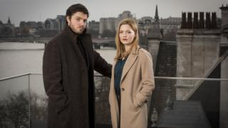 Tom Burke as Cormoran Strike and Holliday Grainger as Robin Ellacott