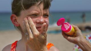 child having sunscreen put on face