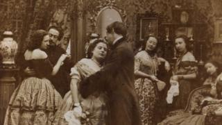 Victorian couples kissing underneath the mistletoe