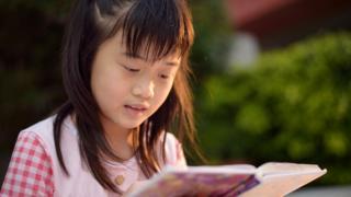 Menina de Cingapura lendo.