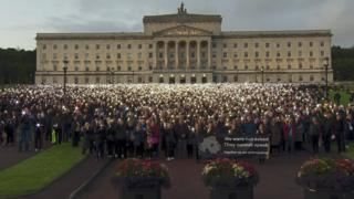 Protesters stand in front of Stormont shining torches