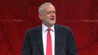 """Jeremy Corbyn wearing a dark coloured suit and white shirt. He is wearing a red tie - and standing in front of a red board which has the words """"Standing up for Wales"""" written on it."""