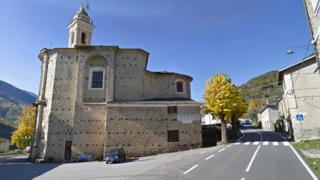 A Google Street view image of the town of Acquetico, showing an old stone church and a single pedestrian crossing