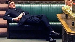 Jacob Rees-Mogg lying on chairs in Parliament