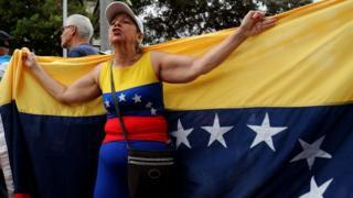 An opposition demonstrator holding a Venezuelan flag behind her back in Caracas