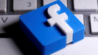 A small tile of the Facebook logo is seen placed on a keyboard in this close-up show