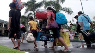 Orang-orang membawa barang-barang mereka berjalan menuju tempat perlindungan sementara di sekolah di kota Tabaco, Filipina. Foto: 24 Desember 2016
