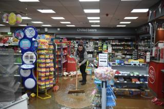A man sweeps up flood water in a convenience store in Tenbury Wells in western England, after the River Teme broke its banks.