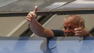 Former President Lula gestures from prison window