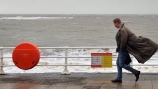 A man walks along the promenade in Aberystwyth, Wales, on 17 November