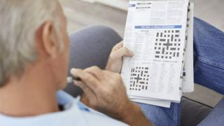Man doing crossword puzzles