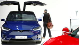 A visitor inspects a Tesla Model X electric vehicle at Brussels Motor Show, Belgium, January 18, 2019.