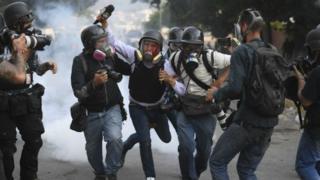 Травмованому журналісту допомагають інші під час вуличного протесту у Венесуелі